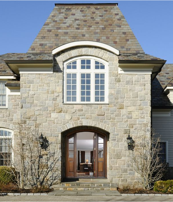 a stone mansion with an open heavy wooden door